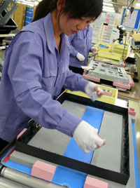 The next worker prepares the front bezel and adds cushioning material before placing the LCD panel inside.