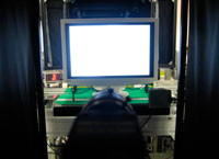 Once assembly is complete, each monitor undergoes an initial screen check inside of an image inspection apparatus. Inside black curtains, a CCD camera automatically determines if the monitor is displaying an image correctly.